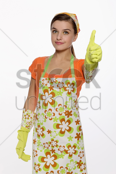 woman in apron showing thumbs up stock photo