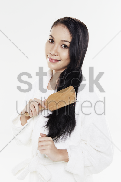 woman in bathrobe brushing her hair stock photo