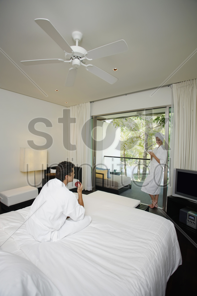 woman in bathrobe holding a cup of tea, man eating apple in bed stock photo