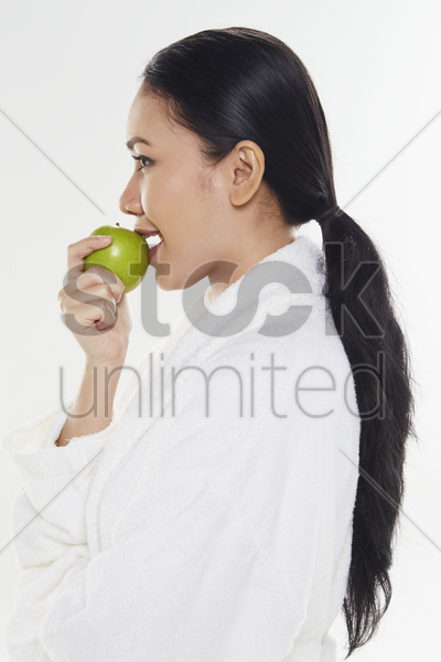 woman in bathrobe holding a green apple stock photo