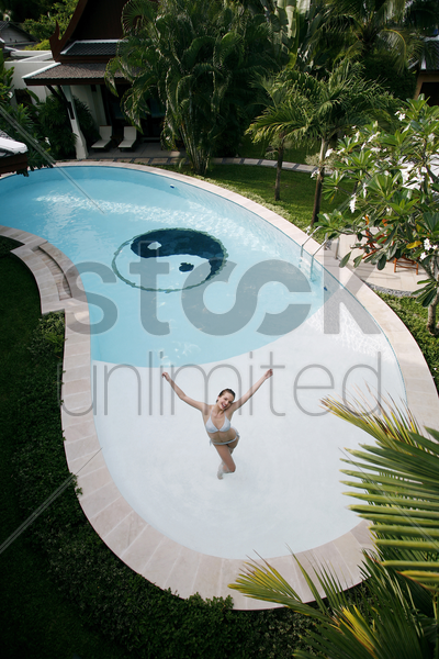 woman in bikini jumping in the pool stock photo