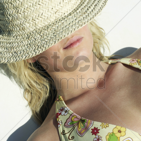 woman in bikini with straw hat covering her eyes stock photo
