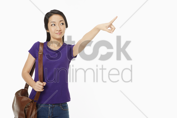 woman in casual clothing pointing to the left stock photo