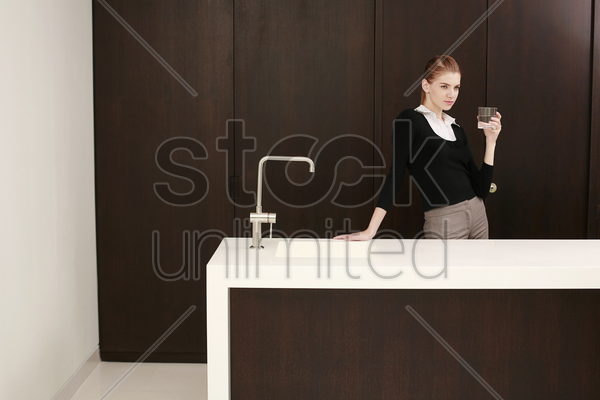 woman in formal wear holding a glass of water stock photo