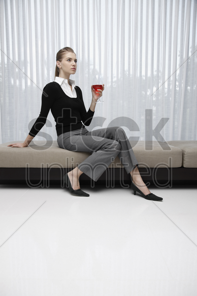 woman in formal wear holding a glass of wine stock photo