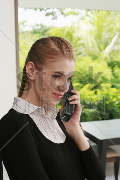 woman in formal wear talking on cordless phone stock photo
