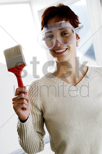 woman in goggles holding a paintbrush stock photo