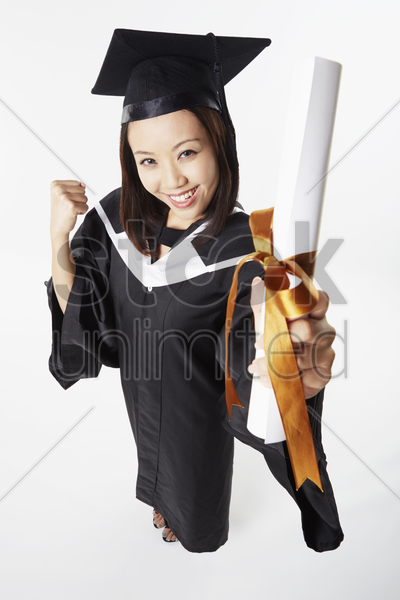 woman in graduation gown cheering stock photo