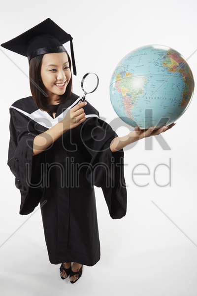 woman in graduation gown holding a magnifying glass and a globe stock photo