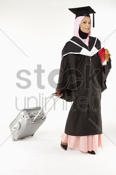 woman in graduation robe going on vacation stock photo