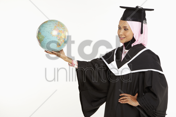woman in graduation robe holding a globe stock photo