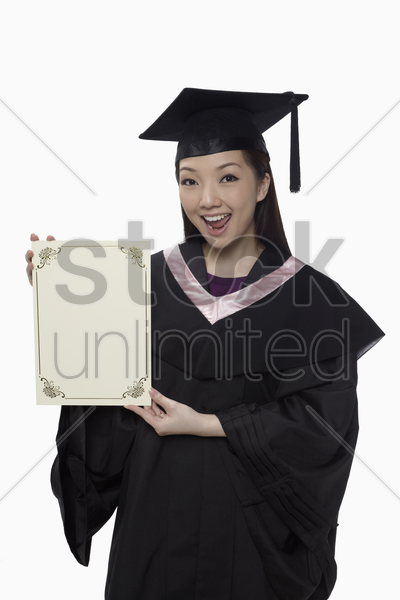 woman in graduation robe holding blank certificate stock photo