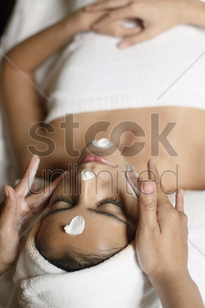 woman in health spa, having cream applied to face stock photo