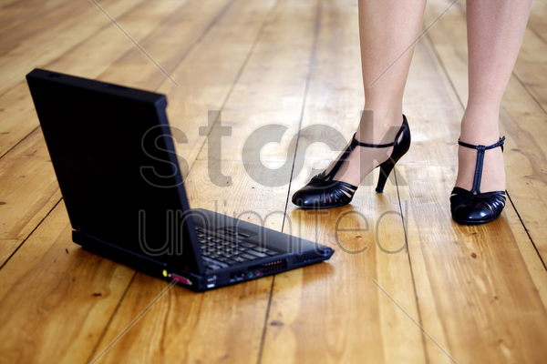 woman in high heels with laptop on the floor stock photo