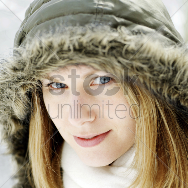 woman in hooded jacket smiling at the camera stock photo