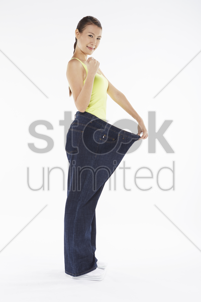 woman in over sized jeans stock photo