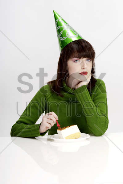 woman in party hat eating cake stock photo