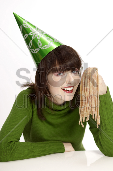 woman in party hat holding licorice stock photo