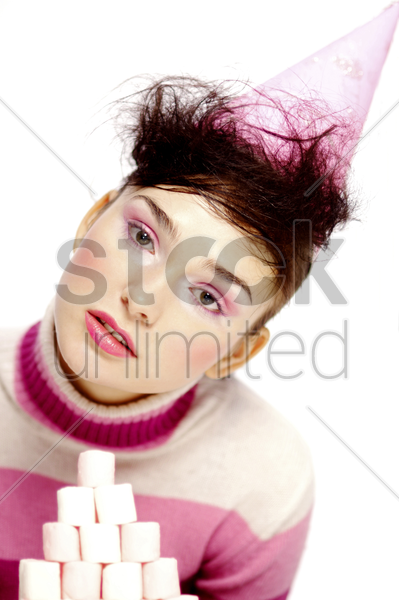 woman in party hat posing in front of a stack of marshmallows stock photo