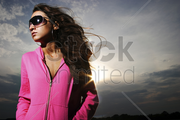 woman in pink jacket and sunglasses stock photo