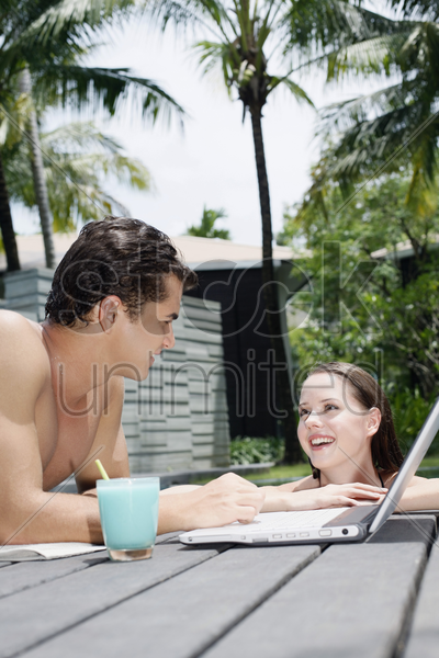 woman in pool talking to man stock photo