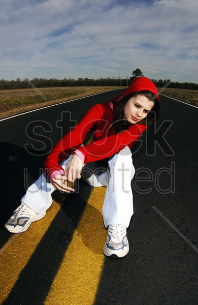 woman in red hooded jacket sitting in the middle of the road stock photo