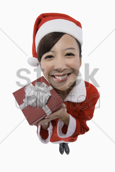 woman in santa suit holding present stock photo