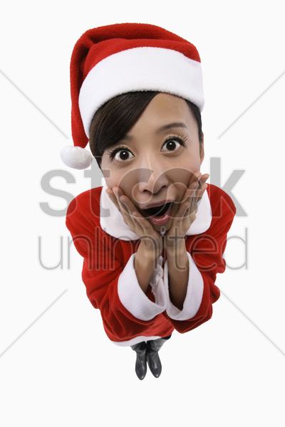 woman in santa suit looking surprised stock photo
