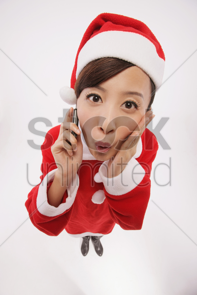 woman in santa suit talking on the mobile phone stock photo