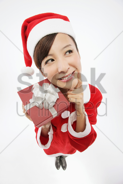 woman in santa suit thinking while holding present stock photo