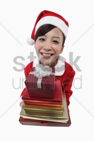 woman in santa suit with a stack of gift boxes stock photo