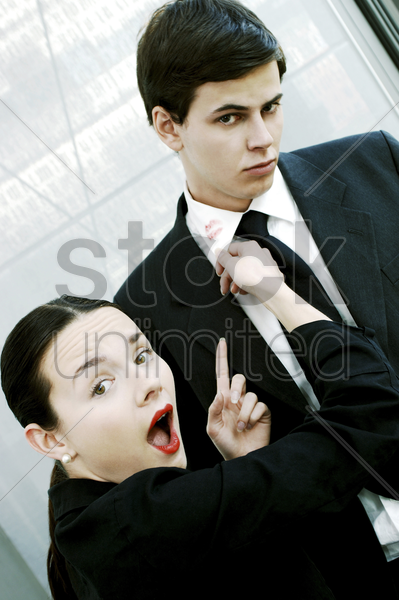 woman in shock upon seeing a lipstick stain on her boyfriend's collar stock photo