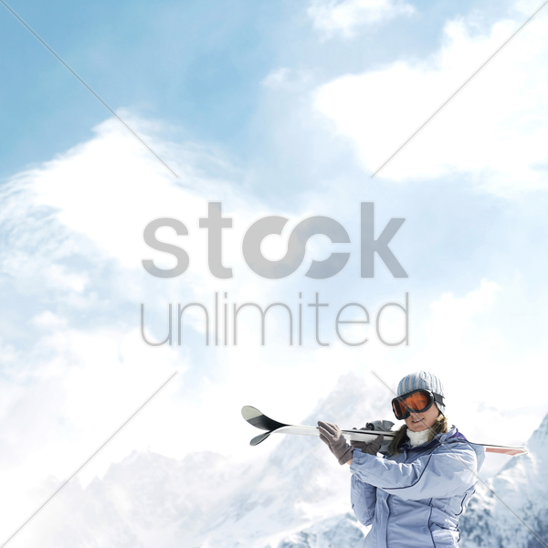 woman in ski goggles holding skis stock photo