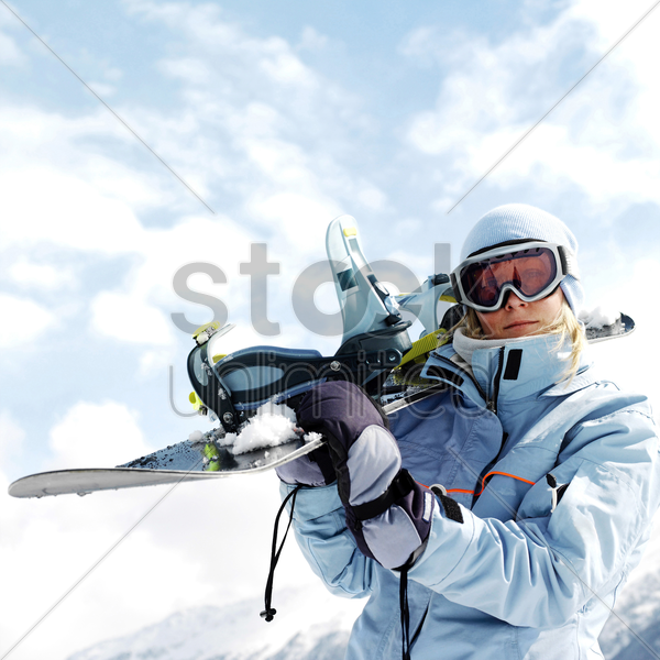 woman in ski goggles holding snowboard stock photo