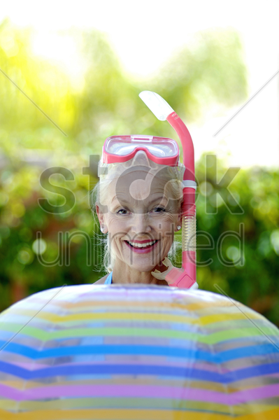 woman in snorkeling goggles holding a beach ball stock photo