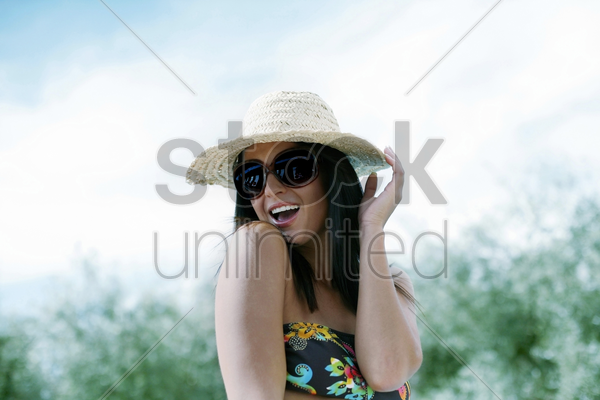 woman in straw hat and sunglasses posing for the camera stock photo