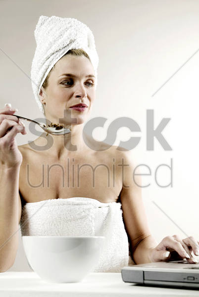 woman in towel eating while using laptop stock photo