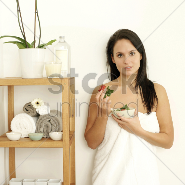 woman in towel holding a bowl of strawberries stock photo