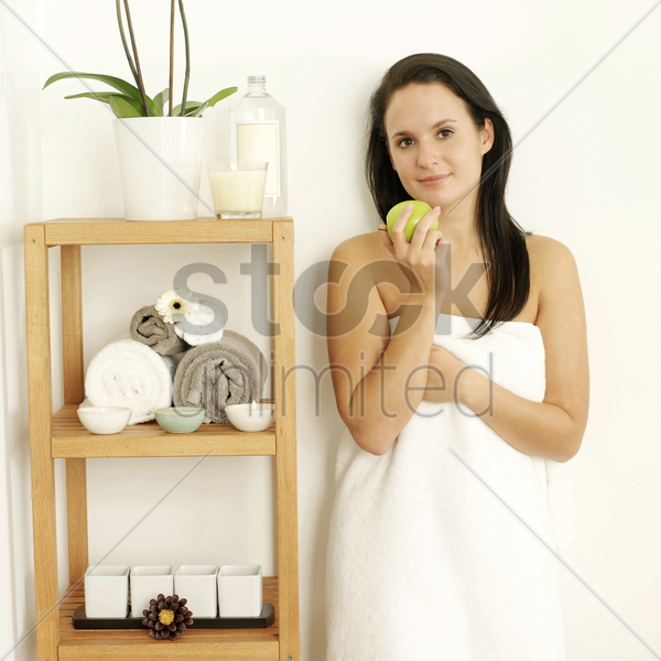 woman in towel holding a green apple stock photo