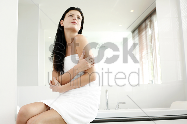 woman in towel sitting on the bathtub ledge stock photo