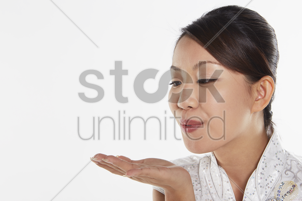 woman in traditional clothing blowing a kiss stock photo