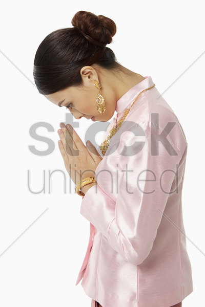 woman in traditional clothing bowing her head stock photo