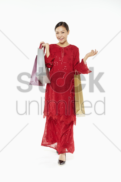 woman in traditional clothing carrying shopping bags stock photo
