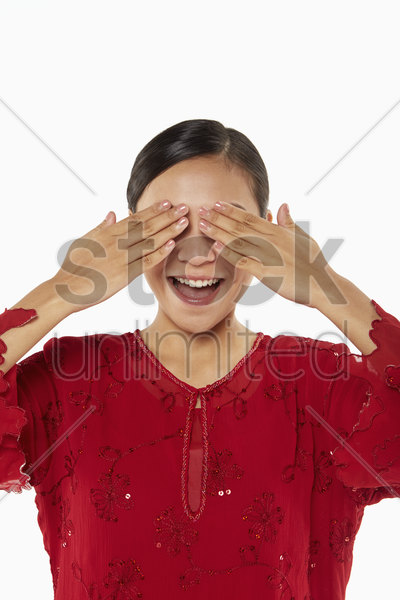 woman in traditional clothing covering eyes stock photo