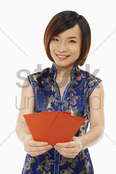 woman in traditional clothing giving out red packets stock photo
