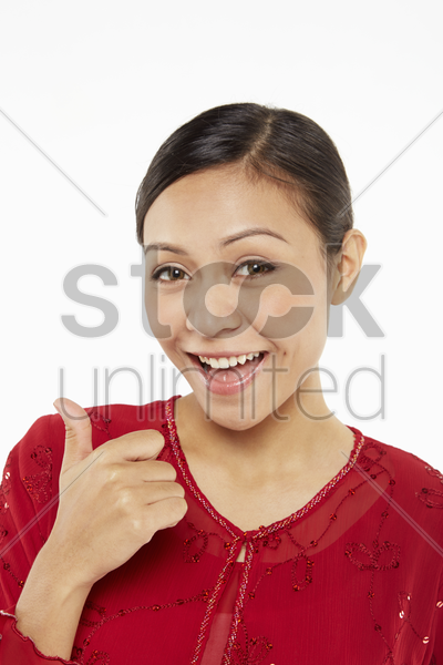 woman in traditional clothing giving thumbs up stock photo