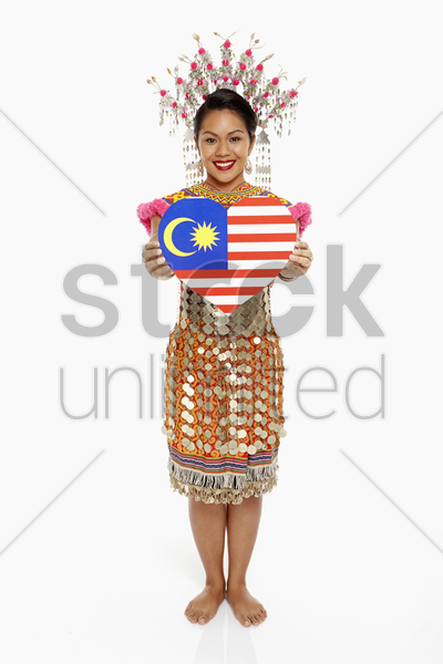 woman in traditional clothing holding a heart shape stock photo