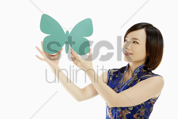 woman in traditional clothing holding a paper butterfly stock photo