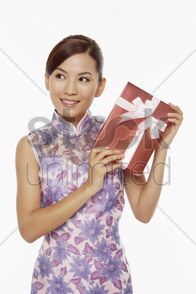 woman in traditional clothing holding a red gift box stock photo