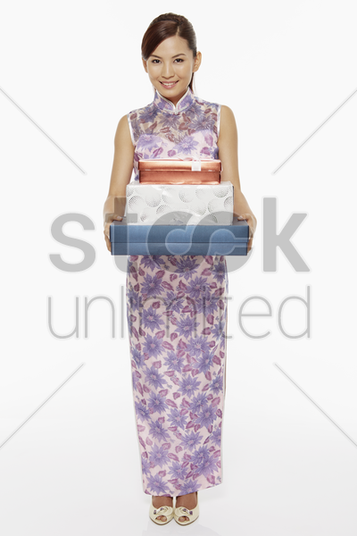 woman in traditional clothing holding a stack of gift boxes stock photo
